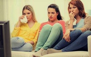 3 women watching a movie at home